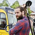 Ein junger Mann in karriertem Hemd trägt ein Fahrrad über der Schulter. Im Hintergrund sieht man eine Bahn der KVV.