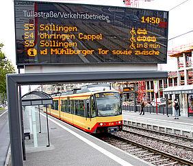 Eine digitale Fahrgastanzeige zeigt verschiedene Bahnen und deren Abfahrtszeiten. Im Hintergrund ist eine Stadtbahn an einer Haltestelle zu sehen.