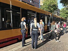 Polizisten vor einer Bahn, bereit zur Kontrolle der Maskenpflicht.