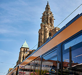 Ein fenster einer AVG-Stadtbahn. Im Hintergrund ist ein Kirchturm in der Heilbronner Innenstadt zu sehen.