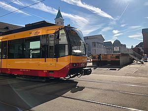 Eine gelbe Stadtbahn beim Vorbeifahren am Marktplatz in Karlsruhe. Der Himmel ist blau und leicht bewölkt.