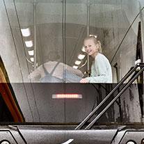 Mädchen sitzt in der davonfahrenden Bahn und lächelt.