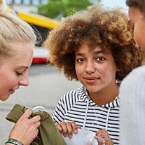 3 Freundinnen nach dem Shopping. Ein Mädchen mit braunen Locken schaut direkt in die Kamera.
