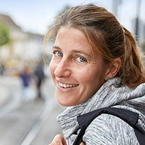 Eine lächelnde Frau an einer Bahnhaltestelle.