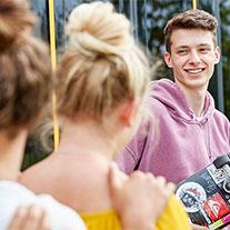 Eine Gruppe Jugendlicher stehen vor einer Bahn.